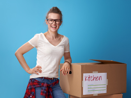 Portrait of smiling active woman in white shirt standing next to the cardboard boxes isolated on blue Stockfoto