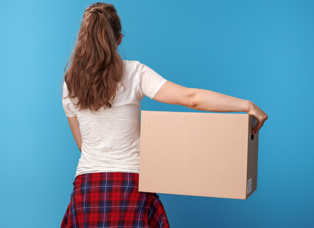 Seen from behind active woman in white shirt with a cardboard box against blue background Stock Photo