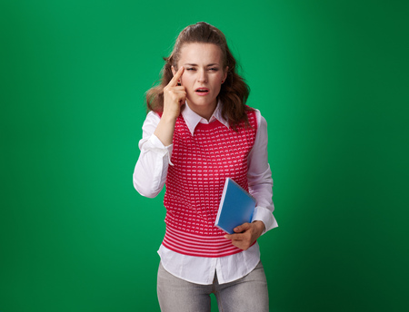 modern student woman in a red waistcoat with a blue notebook squinting eyes to see better against green background Stock Photo