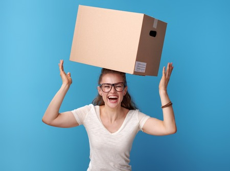 Portrait of happy active hipster in white shirt with a cardboard box on head isolated on blue background