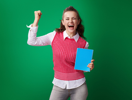 smiling young student woman in a red waistcoat with a blue notebook rejoicing on green background