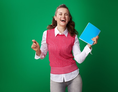 happy modern student woman in a red waistcoat with a blue notebook dancing isolated on green background Banco de Imagens