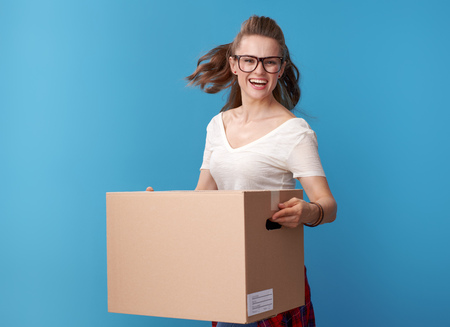 Portrait of cheerful woman in white shirt with a cardboard box on blue background
