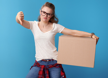 unhappy modern hipster in white shirt with a cardboard box showing thumbs down on blue background Stock Photo