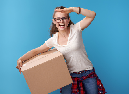 smiling active hipster in white shirt with a cardboard box looking into the distance against blue background