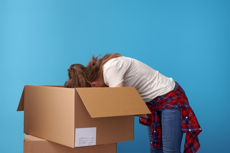 modern hipster in white shirt looking for something in the a cardboard box against blue background Standard-Bild