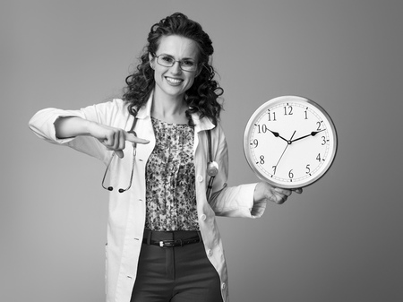 happy paediatrician doctor in white medical robe pointing at clock against background