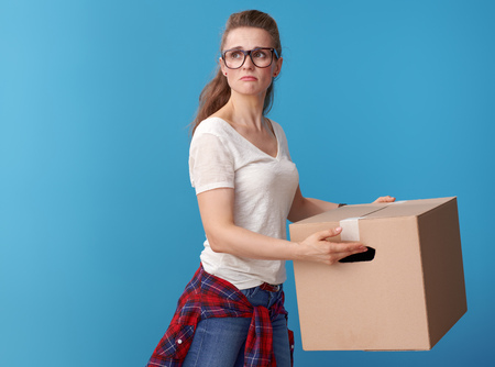 unhappy active woman in white shirt with a cardboard box looking back on blue background Stock Photo