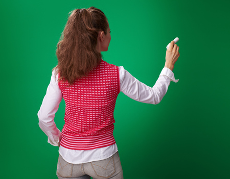 Seen from behind modern student woman in a red waistcoat writing with a piece of chalk on green background