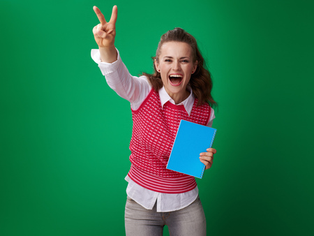 happy modern student woman in a red waistcoat with a blue notebook showing victory gesture on green background