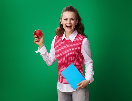 happy young student woman in a red waistcoat with a blue notebook and an apple isolated on green