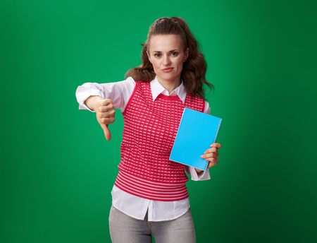 unhappy young student woman in a red waistcoat with a blue notebook showing thumbs down isolated on green Stock Photo