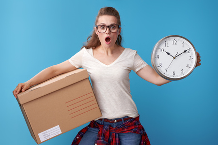 shocked young woman in white shirt with a cardboard box showing clock isolated on blue