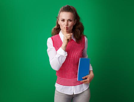 moderne Studentin in einer roten Weste mit einem blauen Notizbuch, das shh Geste lokalisiert auf Grün zeigt