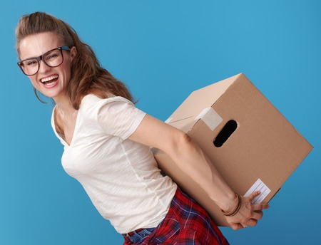 happy young woman in white shirt holding a cardboard box behind back isolated on blue background Фото со стока