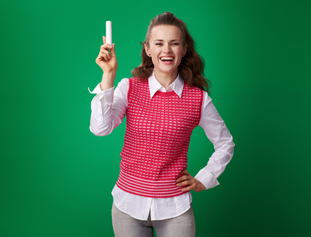 smiling modern student woman in a red waistcoat showing a piece of chalk on green background