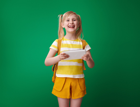 smiling pupil with backpack using tablet PC against green background Stockfoto