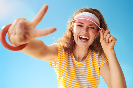 smiling fit woman in yellow shirt against blue sky showing victory gesture 版權商用圖片