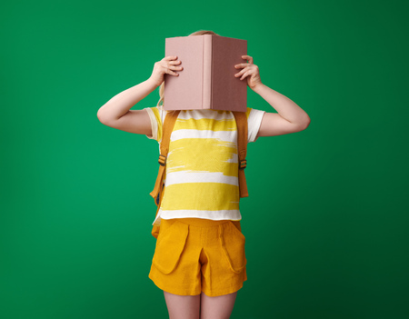 pupil with backpack hiding behind a book on green background Stockfoto