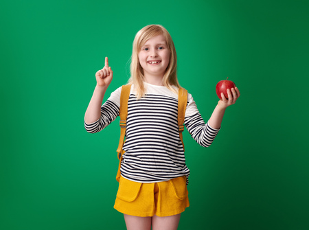 happy pupil with backpack with an apple got idea on green background