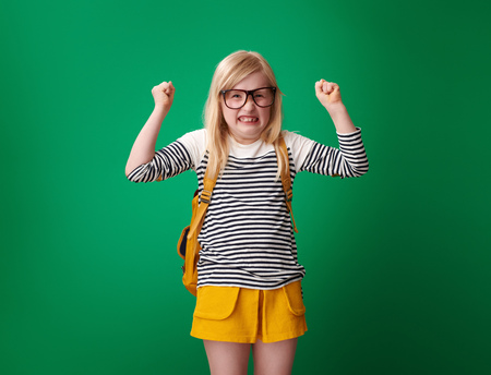 Portrait of angry school girl with backpack isolated on green background