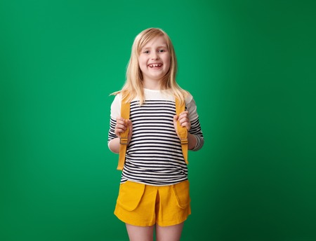 Portrait of happy pupil with backpack isolated on green Stockfoto