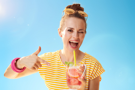 smiling healthy woman in yellow shirt against blue sky pointing at refreshing cocktail