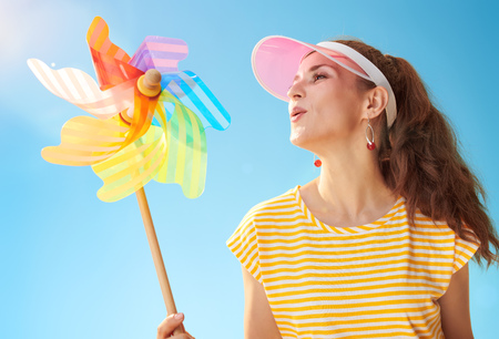 smiling fit woman in yellow shirt against blue sky blowing on colorful windmill