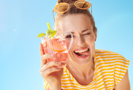 cheerful healthy woman in yellow shirt against blue sky with refreshing cocktail