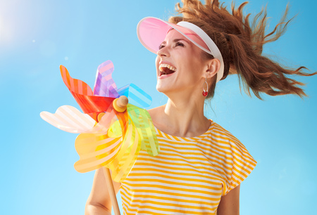 happy fit woman in yellow shirt against blue sky with colorful windmill looking aside Фото со стока