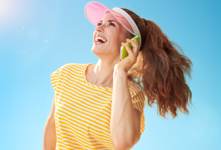 smiling healthy woman in yellow shirt against blue sky looking aside and using a cell phone Stok Fotoğraf
