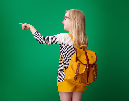 Seen from behind school girl with backpack pointing at something on green background Stock Photo