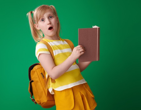 surprised school girl with backpack with an open book on green background