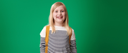 smiling school girl with backpack isolated on green
