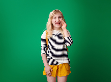 happy school girl with backpack telling exciting news isolated on green background