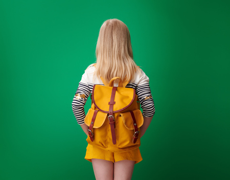 Seen from behind pupil with backpack against green background