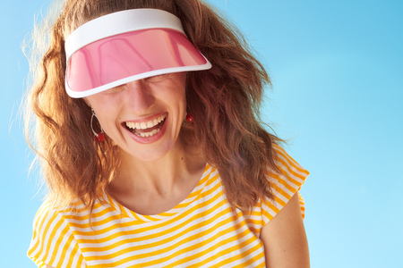 happy healthy woman in yellow shirt against blue sky hiding behind sun visor Stok Fotoğraf