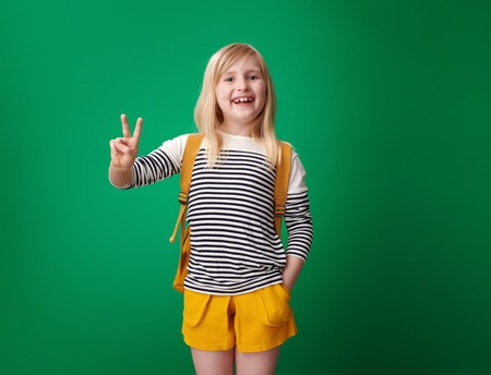 smiling pupil with backpack showing victory gesture isolated on green background