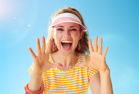 happy healthy woman in yellow shirt against blue sky shouting through megaphone shaped hands