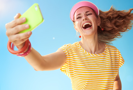 smiling fit woman in yellow shirt against blue sky taking selfie with mobile phone