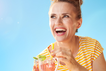 happy healthy woman in yellow shirt against blue sky with refreshing cocktail looking aside