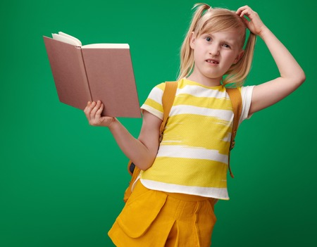 pensive pupil with backpack with an open book on green background Stock Photo
