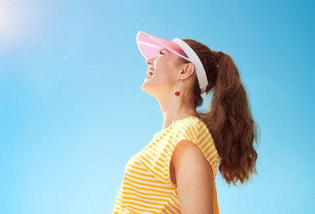 Portrait of smiling healthy woman in yellow shirt against blue sky looking up at copy space