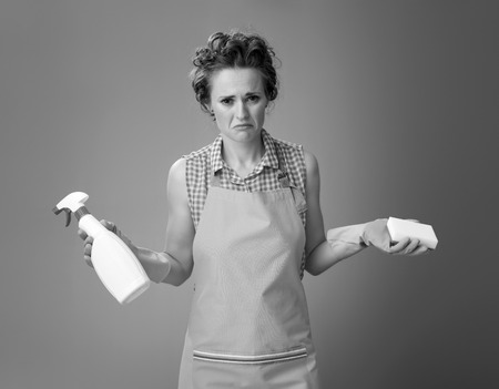Big cleaning time. unhappy young housewife with rubber gloves and kitchen sponge and a bottle of detergent isolated on