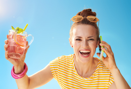 Portrait of smiling active woman in yellow shirt against blue sky with refreshing cocktail using a mobile phone