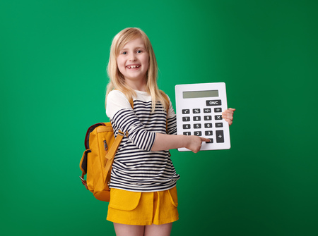 happy pupil with backpack pointing at a equally key on the calculator on green background 스톡 콘텐츠