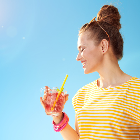 smiling healthy woman in yellow shirt against blue sky drinking refreshing cocktail