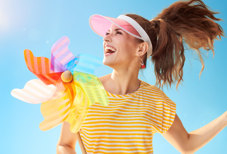 cheerful healthy woman in yellow shirt against blue sky playing with colorful windmill