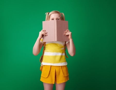 school girl with backpack hiding behind an open book on green background