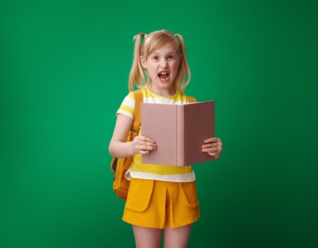 annoyed school girl with backpack with an open book on green background
